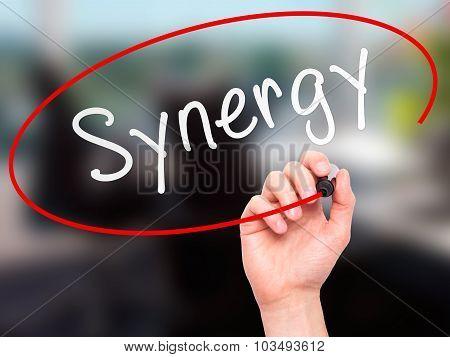 Man Hand writing Synergy black marker on visual screen.
