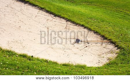 Sand Bunker On Golf Course And Rake