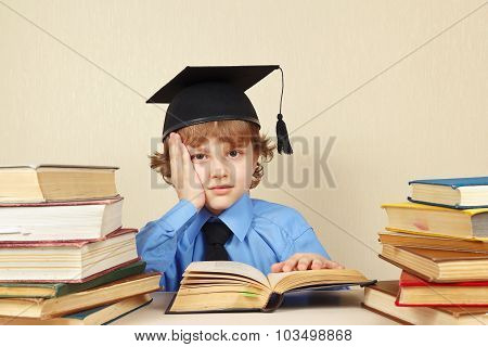 Little tired boy in academic hat studies old books