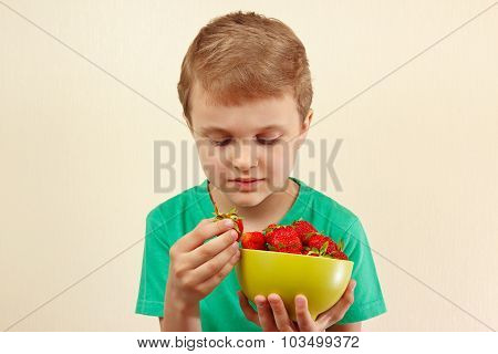 Little boy takes fresh strawberry from the bowl