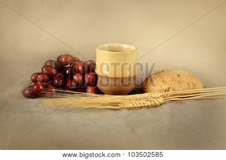 Communion table with cup of wine, grapes, bread and wheat