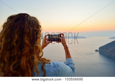SANTORINI, GREECE - AUGUST 07, 2015: Woman take photo of Santorini island. It is the largest island of a small, circular archipelago which bears the same name and is the remnant of a volcanic caldera