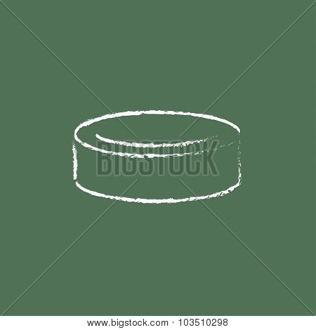 Hockey puck hand drawn in chalk on a blackboard vector white icon isolated on a green background.