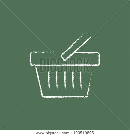 Shopping basket hand drawn in chalk on a blackboard vector white icon isolated on a green background.