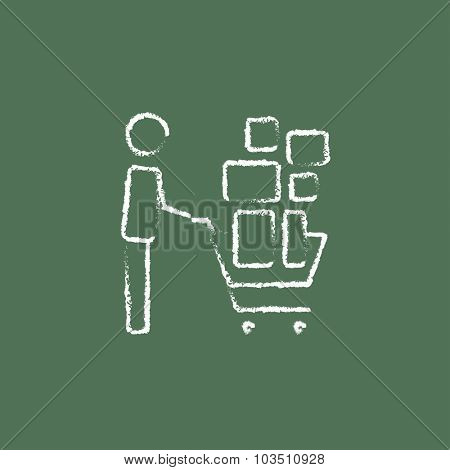 Man pushing shopping cart hand drawn in chalk on a blackboard vector white icon isolated on a green background.