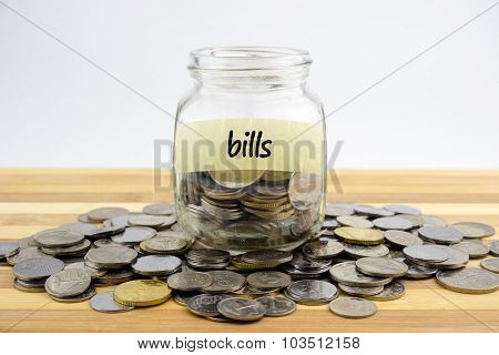 Coins In Glass Container With Bills Label On Wooden Surface Against White Background.financial Conce