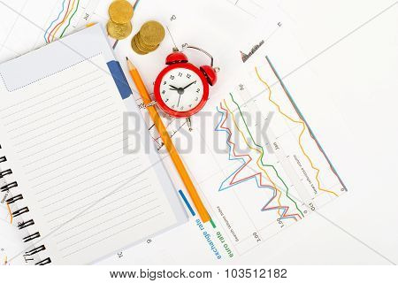 Red alarm clock with notebook and pencil