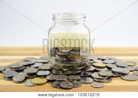 Coins In Glass Container With Blank Label On Wooden Surface Against White Background.financial Conce