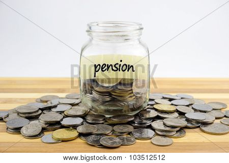 Coins In Glass Container With Pension Label On Wooden Surface Against White Background.financial Con