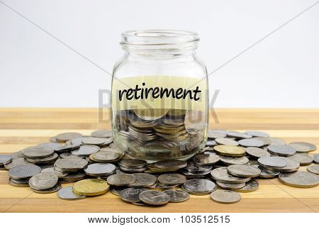 Coins In Glass Container With Retirement Label On Wooden Surface Against White Background.financial