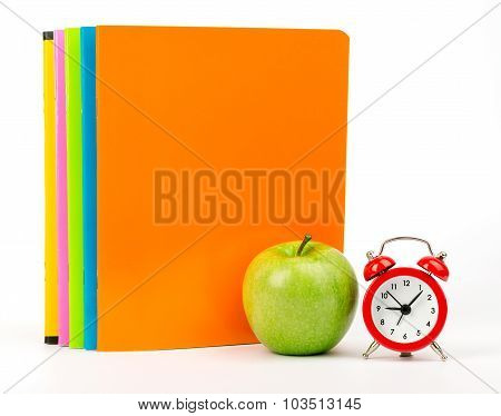 Apple with exercise books and alarm clock