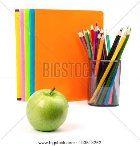 Copybooks with fresh apple and crayons