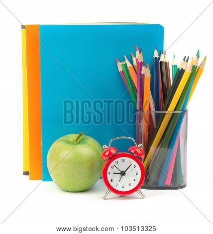 Copybooks with green apple and alarm clock