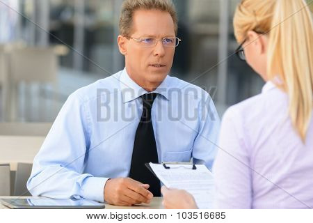 Pleasant businesswoman talking to the colleague
