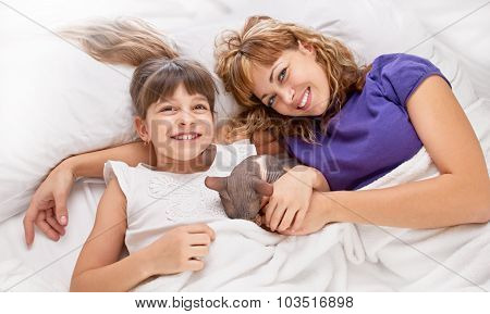 Mother playing with daughter on the bed