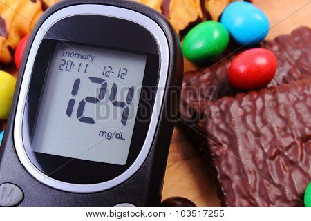 Glucose Meter With Heap Of Sweets, Diabetes And Unhealthy Food