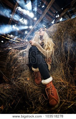 Beautiful woman relaxing in straw in smoky room