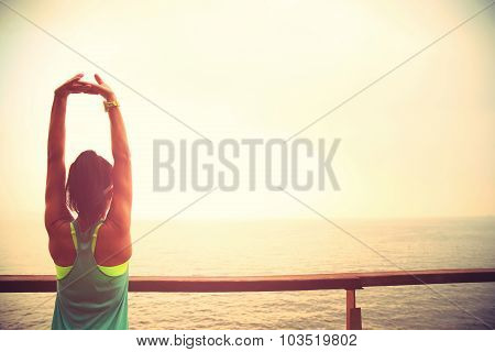 fitness sports woman runner stretching on wooden boardwalk seaside