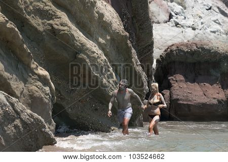 Paros, Greece, 09 August 2015. Couple at Kalogeros beach taking a healing mud bath with clay.
