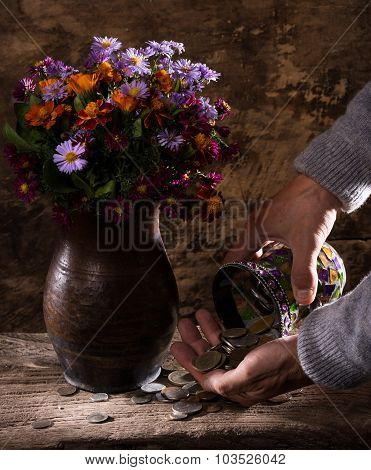 Flowers in vase caucasian old man's hands and pile of old coins