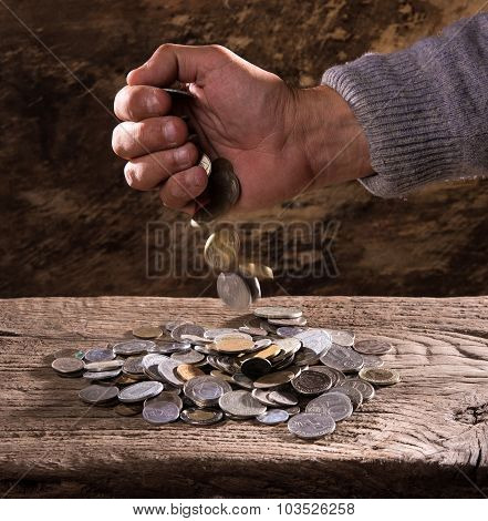 caucasian old man's hands and pile of old coins