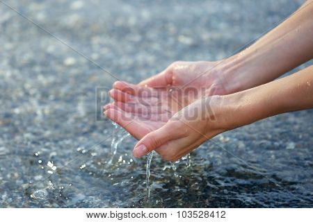Female hands touching sea water