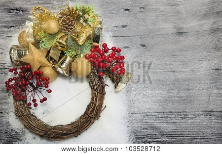 Christmas wreath with golden balls, bells, snow  and red berries  on the wooden background