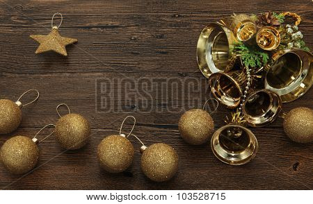 Glittering gold Christmas balls, bells, and star on wooden background