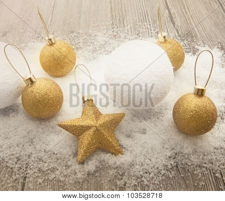 Glittering gold Christmas balls, snowballs, winter snow and star on wooden background