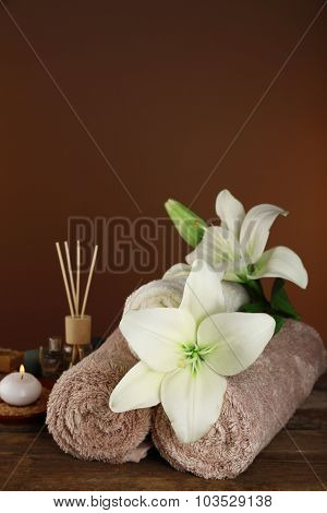 Beautiful spa composition with lily on brown background