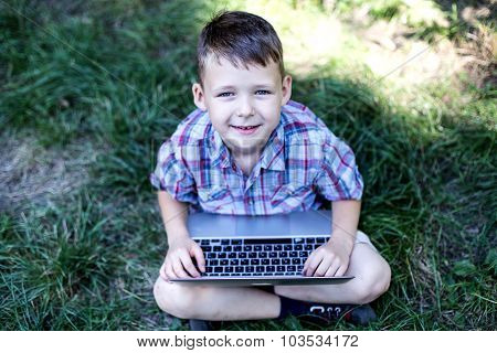 Happy child looking at the camera and playing on the computer