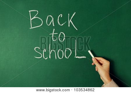 Female hand writing on blackboard with chalk, close up