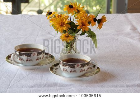 Two Cups Of Coffee And Bunch Of Flowers