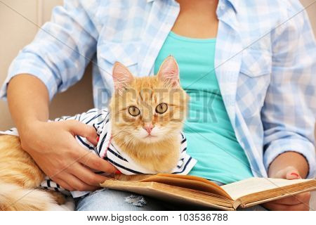 Young woman holding cat and book, close-up