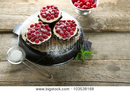 Sweet cakes with raspberries on wooden table background