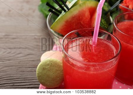 Cold watermelon drinks in glasses, on wooden table background