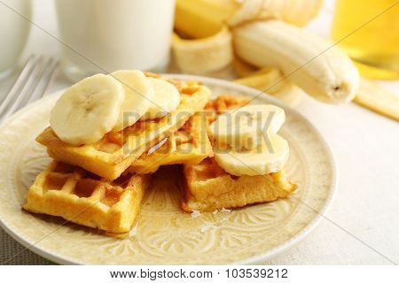 Sweet homemade waffles with sliced banana on plate, on light background
