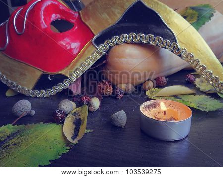 Autumn leaves, pumpkin and a mask with a candle on a dark surface