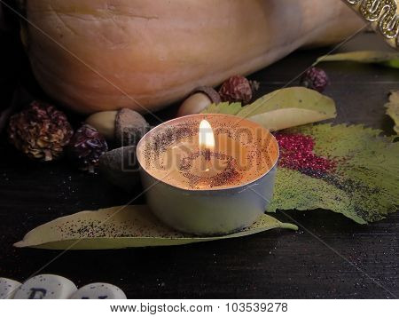 Candle, autumn leaves on a dark surface