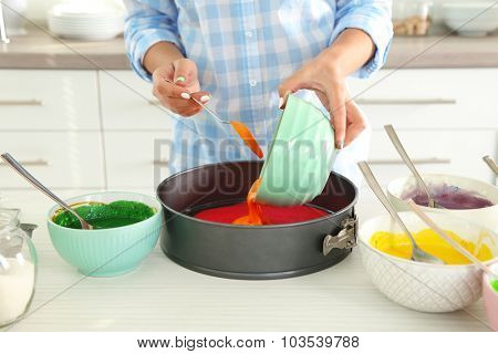 Young woman making rainbow cake in kitchen