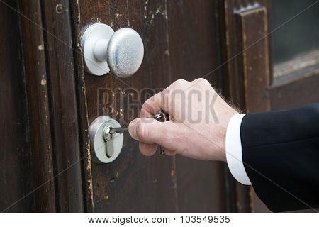 Closeup Of Hand With Key At A Door