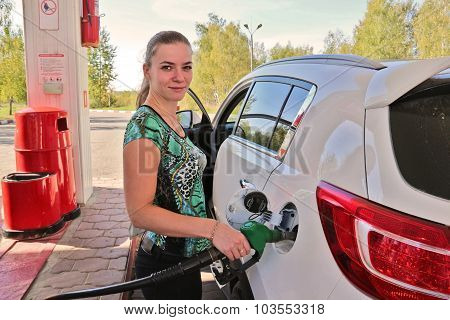 Young Woman-motorist Fills Her Car With Benzine At Gas Station