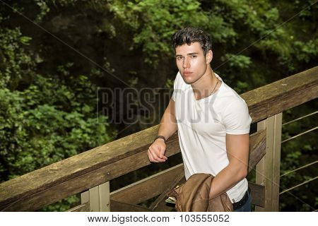 Handsome Young Man Leaning Against Pathway Rail