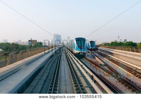 Two Commuter Trains Pass Each Other On Elevated, Parallel Tracks In Urban Dubai.