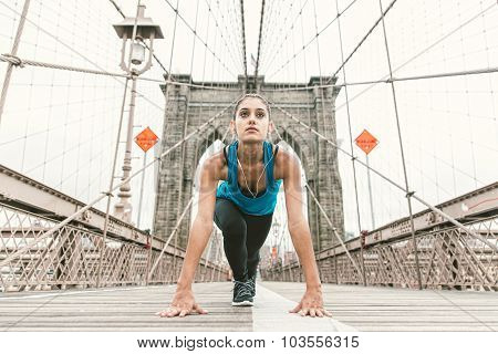 Beautiful Girl Making Stretching At Early Morning Before Running. Brooklyn Bridge And New York Skyli