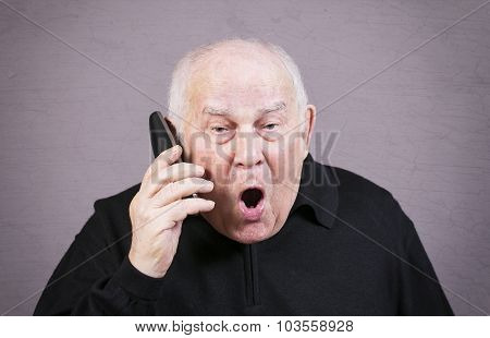 Very emotional old man with the telephone handset screams on a gray background