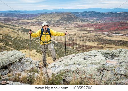 senior male hiker reaching top of a rock cliff and gasping for air, REd MOuntain Open Space near Fort Collins, Colorado, early fall