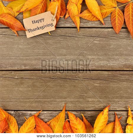 Happy Thanksgiving tag with frame of autumn leaves on wood