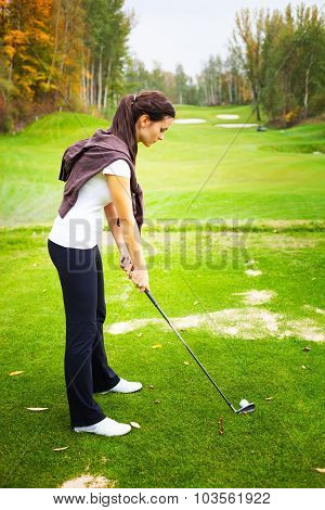 Young Woman Player On Golf Course Preparing To Golf Swing