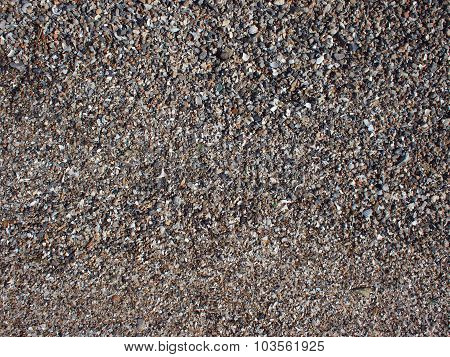 Top View Of Wet Sand And Small Stones With Fragments Of Shells